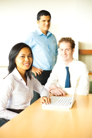 A diverse group of attractive business people smile during a meeting using a laptop led by a beautiful businesswoman.