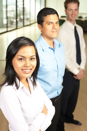 A beautiful asian business woman, and her hispanic and caucasian coworkers stand in a row in a corporate setting. photo