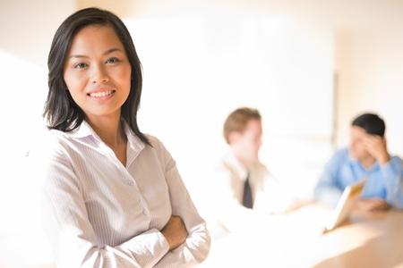 그녀의 작업 동료의 앞에 웃고있는 아름다운 아시아 사업가