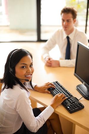 아름 다운 아시아 고객 서비스 에이전트 미소 그녀의 책상에서 고객 봉사하는 동안