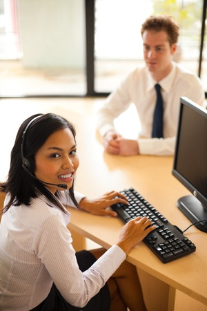 A beautiful asian customer service agent smiles while serving a customer at her desk