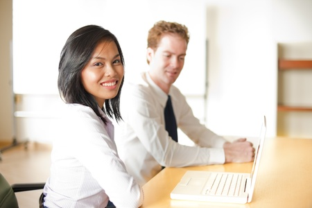 A cute corporate asian businesswoman smiles during a meeting with her caucasian colleague in front of a laptop