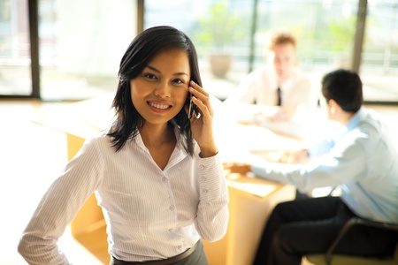 A cheerful asian businesswoman using a smartphone during a meeting with her coworkers photo