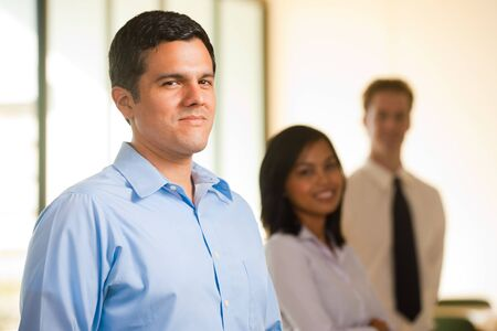A singled out handsome hispanic male heads a line of cheerful colleagues Stock Photo - 9866990