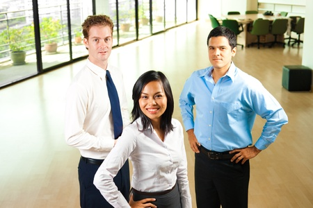 A team of three diverse professional colleagues, a caucasian, asian, and hispanic stand united in a beautiful office environment. Stock Photo - 9866996
