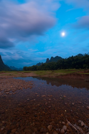 A moon rises during the blue hour over karst landscape reflected in a river bed in Yangshuo, China. photo