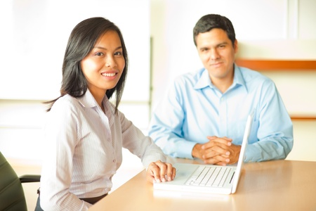 A beautiful young Asian woman leads a meeting with a latino businessman.