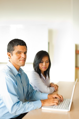 Hispanic male businessman types on a laptop during a one on one meeting with an attractive Asian businesswoman. Stock Photo - 10030750