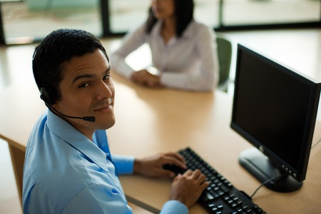 helps: A handsome hispanic male customer service representative helps a young woman at his computer