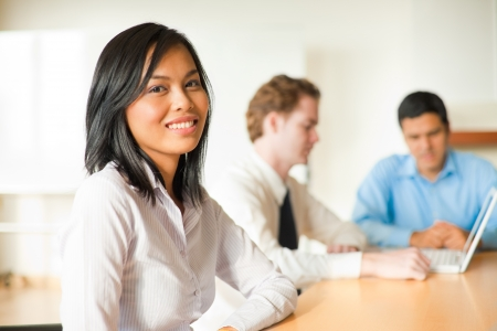 casual caucasian: An attractive Asian businesswoman looks at the camera during a meeting with a diverse group of business people including a latino and caucasian male.