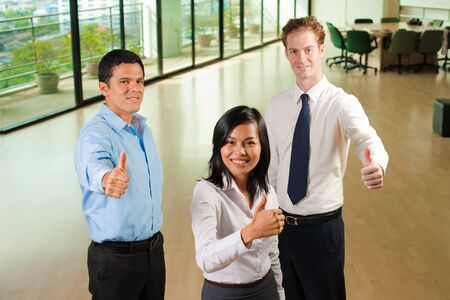 A happy group of three diverse business people each display a cheerful thumbs up for approval.