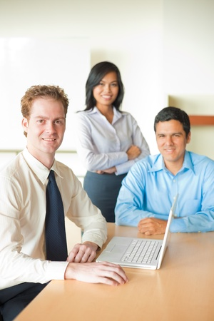 A caucasian businessman leads a team meeting with a handsome latino male and beautiful asian female. Stock Photo