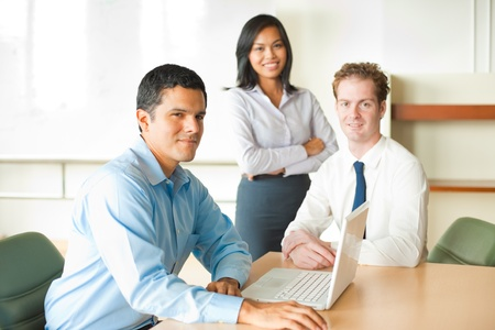 A latino businessman leads a diverse team of business people including an attractive Asian woman and caucasian male. Banque d'images