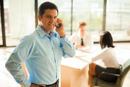 잘 입고 하 고 잘 생긴 히스패닉계 남성 사업가 밝은 사무실에서 회의 중 휴대 전화를 사용합니다. 스톡 콘텐츠