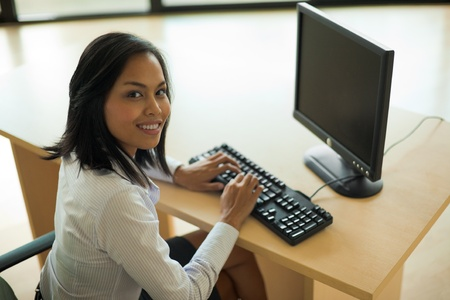 A cute Asian businesswoman works at her computer in a brightly lit office