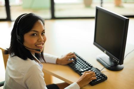귀여운 아시아 고객 서비스 담당자는 그녀의 책상에 컴퓨터에서 작업하는 동안 그녀의 머리에 카메라를 찾고집니다. 스톡 콘텐츠