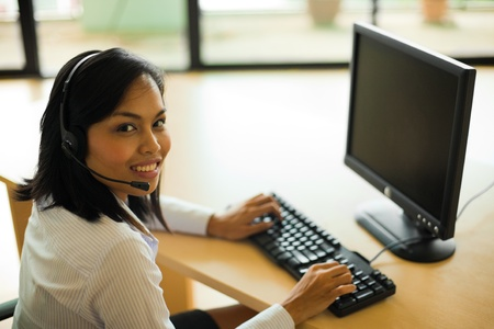 A cute Asian customer service representative turns her head looking into the camera while working at a computer on her desk. Banco de Imagens