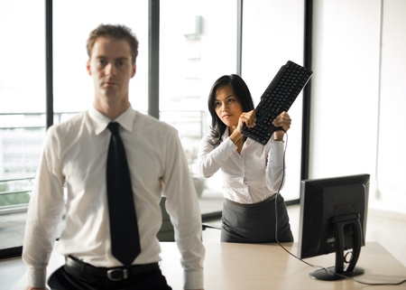 violence in the workplace: A female office employee swings a keyboard to mock hit her male boss over the head. Stock Photo