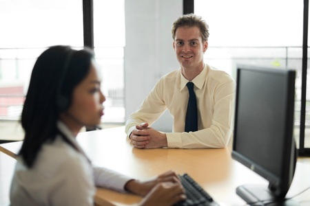 customer service representative: A patient and happy customer looking into the camera in the background is helped by an attractive Asian customer service representative. Stock Photo