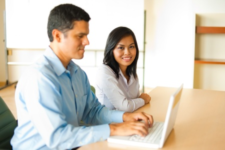 An attractive Asian female looks directly into the camera while meeting with a Hispanic male businessman at a laptop Stock Photo