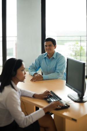A handsome Latino customer looks into the camera while being served by an attractive Asian female customer service representative. photo