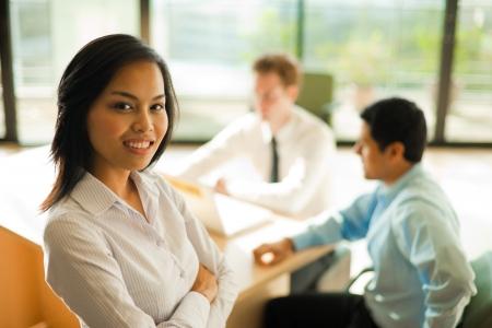 매력적인 아시아 여성 스탠드 및 비즈니스 모임 동안 카메라를 살펴 봅니다.