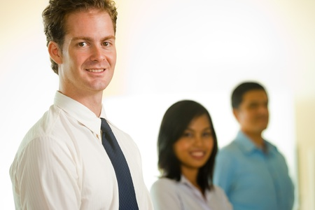 A handsome Caucasian businessman leads a team consisting of an Asian female and Latino male lined up in a row. photo
