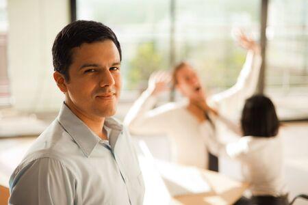violence in the workplace: Un hombre hispano se pone delante de una mujer asfixia a un compa�ero en una muestra de violencia en el trabajo.