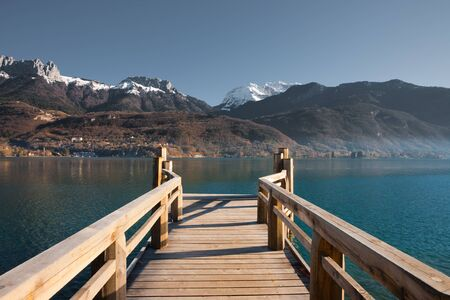 european alps: Snow capped  French Alps mountains seen from a pier on Annecy Lake Stock Photo