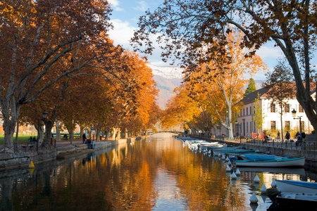 The canal in Annecy, France ringed by the beautifully colored autumn leaves