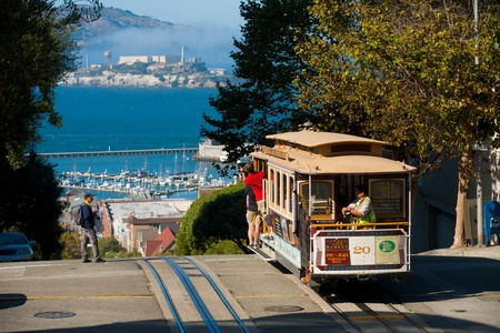 San Francisco, California - September 21:  Tourists ride the iconic cable car on a sunny day at the top of Hyde Street overlooking Alcatraz in San Francisco.  The cable car system is at the heart of any tourist visit to San Francisco  September 21, 2011 a
