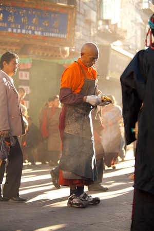 focal point: Lhasa, Tibet, China - October 17, 2007: A Tibetan Buddhist man collects a donation during his morning prostration around the Barkhor, a focal point of Tibetan pilgrims, on October 17, 2007 in Lhasa, Tibet.