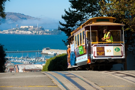 San Francisco, USA - September 21, 2011: A cable car, an iconic mode of San Francisco transportation meets an iconic landmark, Alcatraz Prison, at the top of Hyde Street  September 21, 2011 at San Francisco, California, USA