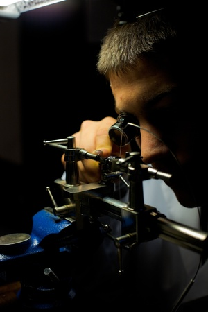 watchmaker: Geneva, Switzerland - November 13: A Swiss watchmaker uses a lathe to grind down a tiny hand-made watch part during The Watches Day, an annual exhibition of Swiss watchmakers November 13, 2011 at Geneva, Switzerland.  Vertical