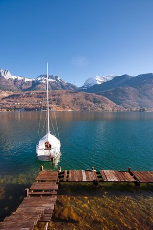 snowcapped: A sailboat is anchored on a pristine alpine lake with snow-capped mountains of the French alps in the background Stock Photo