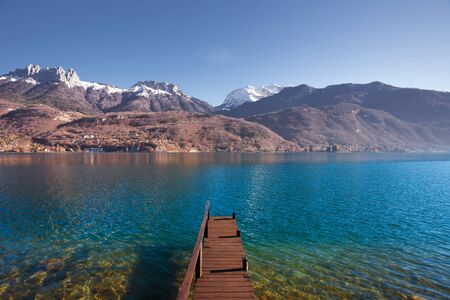 snowcapped: An old wooden pier faces the snow-capped mountains of the French alps on beautiful Lake Annecy.  Horizontal Stock Photo