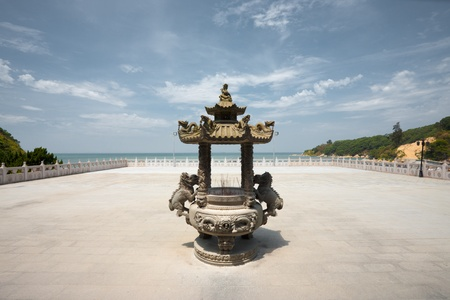 ornately: The courtyard at Matsu temple faces out to the ocean with an ornately carved incense urn Stock Photo