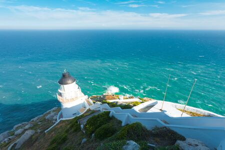The open ocean and the Dongyong lighthouse seen from atop the steep hill behind on Dongyin island on the Matsu archipelago in Taiwan.  Horizontal Banque d'images