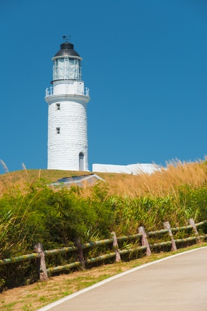 The picturesque white Dongju Lighthouse among a sea of tall grass on Juguang Island on Matsu Islands in Taiwan.