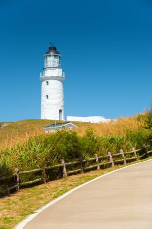 A curving rural country road leads to a picturesque white lighthouse on a hill in a sea of tall grass.  Dongju Island, Matsu Island in Taiwan.