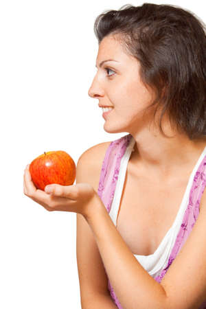 facing: Profile of a casually dressed beautiful woman holding a piece of fruit looking to the side facing sideways.  French-Italian European caucasian female model.  Vertical on isolated white background.