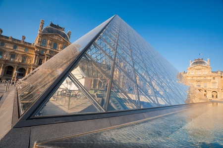 A close tilted view of the Louvre Pyramid, the entrance to the Louvre museum and surrounding historic buildings on a beautiful sunny day.