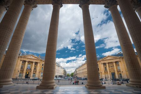 neighboring: The grand columns of the Pantheon and neighboring Parisian buildings are uniquely seen from the inside looking out point of view in Paris, France.