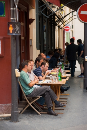 Paris, France - July 6, 2011: Lunch at a Parisian street cafe on a narrow sidewalk. Sidewalk cafes are a daily part of a typical life in Paris July 6, 2011 at Paris, France