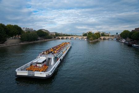 cite: Paris, France - July 9, 2011: A Seine river cruise ship carries tourists and approaches the Ile de la Cite.  Paris is the most tourist visited city in the world.  Horizontal orientation July 9, 2011 at Paris, France