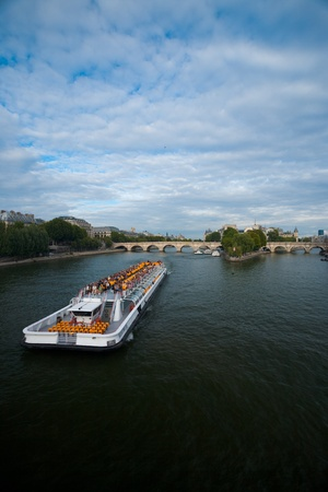 Paris, France - July 9, 2011: A Seine river cruise ship carries tourists and approaches the Ile de la Cite.  Paris is the most tourist visited city in the world.  Vertical orientation July 9, 2011 at Paris, France Stock Photo - 13140156