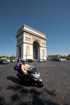 Paris, France - July 5, 2011:  A motorcyclist and passenger take a turn away from the Arc de Triomphe onto Champs dElysees boulevard.  Traffic is a growing concern in center Paris July 5, 2011 at Paris, France