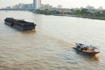 Un petit remorqueur tire une grande barge sur la rivière Chao Phraya à Bangkok, en Thaïlande.