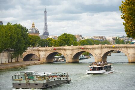 A beautiful cityscape including the Eiffel Tower in the distance with cruise ships passing the pont neuf on the Seine River in Paris, France Stock Photo - 13300030