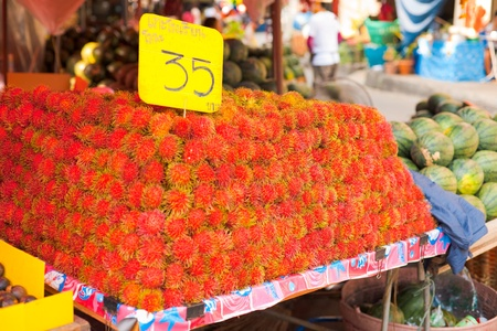 A fruit stand at a local market selling a pile of rambutan, little red spiky tropical fruits found in Bangkok